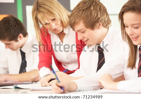Teenage Students Studying In Classroom With Teacher #71234989