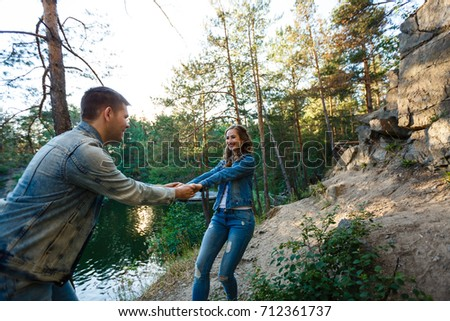 Two young people standing on a rock and holding hands, sunset #712361737