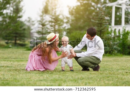 Happiness and harmony family life concept. Young mother and father with baby son in the park. Happy family resting together on the green grass at summer #712362595