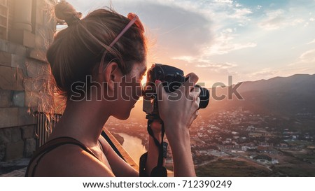 Female photographer, taking pictures of mountain landscape at sunset in Georgia Royalty-Free Stock Photo #712390249