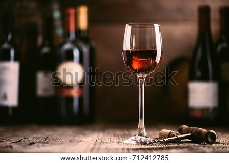 Wine tasting experience in the rustic cellar and wine bar: red wine glass and collection of excellent wines on the background Royalty-Free Stock Photo #712412785