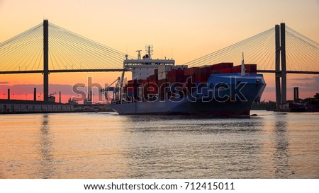 A commercial cargo ship as it leaves the Port of Savannah in Georgia at sunset #712415011