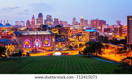 Kansas City, Missouri cityscape skyline as night falls over downtown (logos blurred for commercial use)
