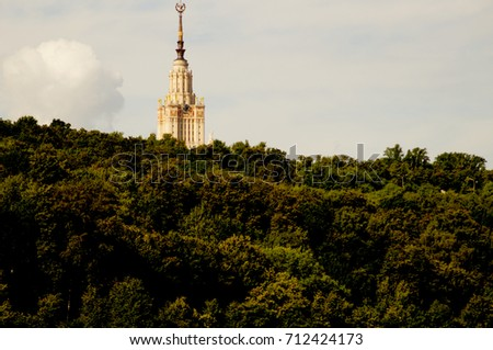 the building is visible beyond the forest #712424173