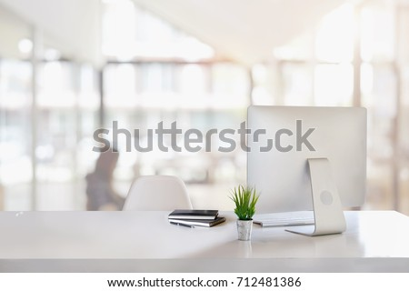 Stylish workspace with desktop computer, office supplies, houseplant and books at office. desk work concept. Royalty-Free Stock Photo #712481386