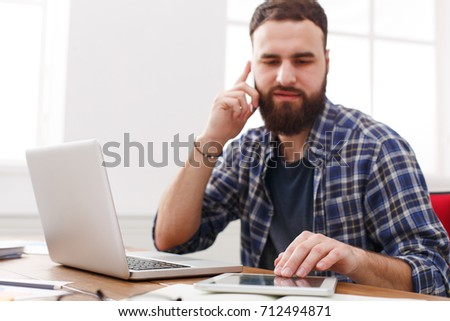 Attractive male office worker is reading report, while is sitting at the table with open net-book. #712494871