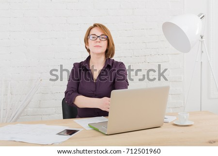 Middle-aged woman in office. Female architect using laptop and smartphone. Redhead caucasian woman in protective glasses with computer. #712501960