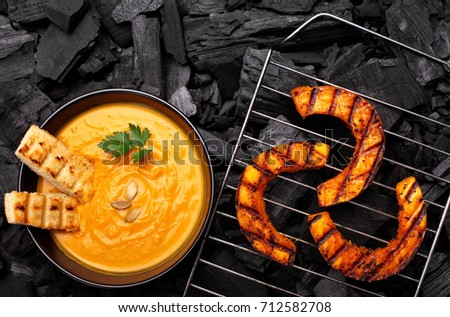 Roasted pumpkin on a grid on charcoal background.BBQ pumpkin.Top view #712582708