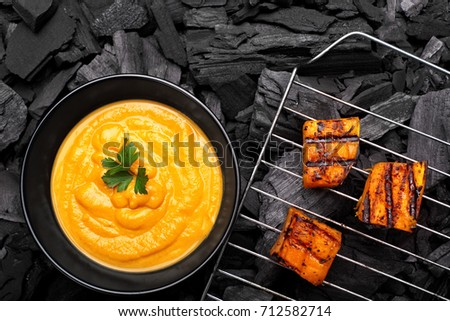 Roasted pumpkin on a grid on charcoal background.BBQ pumpkin.Top view #712582714