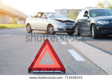 Reflective red triangle to point out a car crash  Royalty-Free Stock Photo #712608241