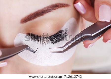 Eyelash Extension Procedure. Woman Eye with Long Eyelashes. Lashes, close up, macro, selective focus. #712613743