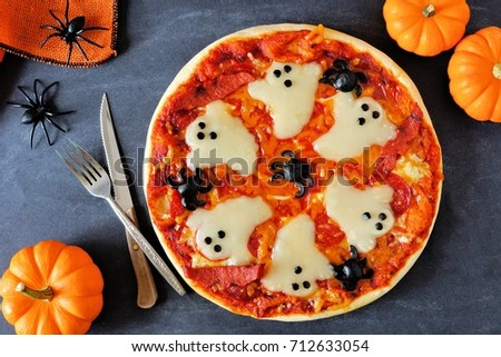 Halloween pizza with ghosts and spiders, above scene with decor on a black background