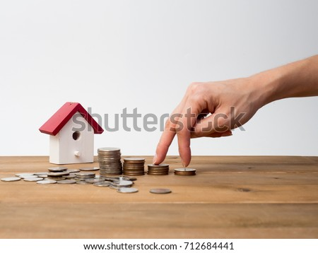 Money coins stack growing with red house on wood background. Business growth investment and financial concept ideas.Real estate investment. House and coins on table.Save money with stack coin. #712684441
