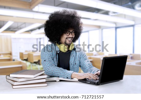Picture of an Afro college student is studying with a laptop and books while sitting in the classroom #712721557