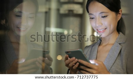 Business woman reply client email on cellphone with window reflection  #712737775