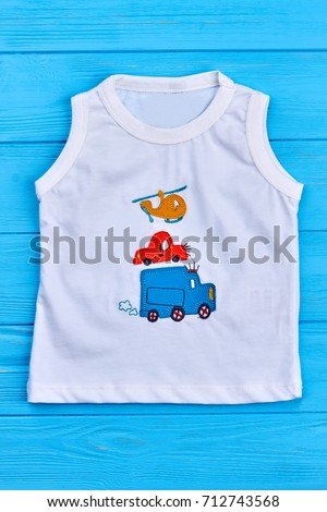 White cartoon baby boy t-shirt. Natural cotton toddler boy white t-shirt with cars and helicopter print on blue wooden background, vertical image.