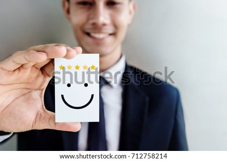 Customer Experience Concept, Happy Businessman holding Card with Smiley Face and Five Star Rating for his Satisfaction Royalty-Free Stock Photo #712758214