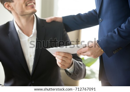 Company leader giving money bonus in paper envelope to happy smiling office worker, congratulating employee with increasing of salary or promotion, thanking for successes in work. Close up concept  #712767091