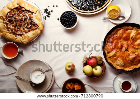 Traditional autumn pies arranged on white linen fabric. Chanterelle mushrooms, blueberry and sweet apple fillings. Top view, copy space. #712800790