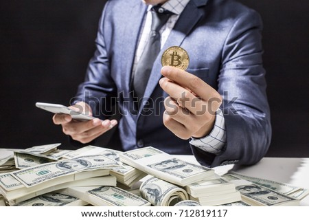 Businessman receive a lot of Money from Smartphone, Businessman Holding Bitcoin Isolated on black background, Digital Money and Bitcoine Concept. #712819117