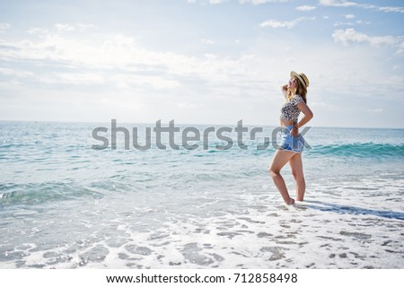 Beautiful model relaxing on a beach of sea, wearing on jeans short, leopard shirt and hat. #712858498