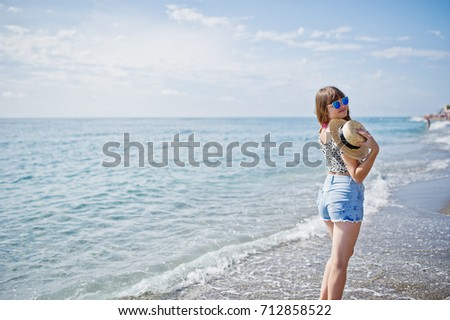 Beautiful model relaxing on a beach of sea, wearing on jeans short, leopard shirt and hat. #712858522