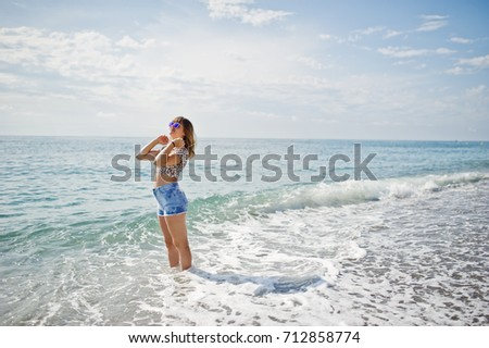 Beautiful model relaxing on a beach of sea, wearing on jeans short, leopard shirt and sunglasses. #712858774