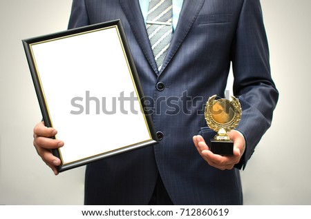 Top manager award mockup. Best office employee award. Business man holding empty blank photo frame (gratitude letter) in one hand and gold medal in another one. Gratitude concept. Grateful letter. #712860619