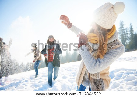 Young couple in snowball fight
