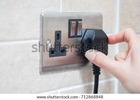 Hand Putting Plug Into Electricity Socket Royalty-Free Stock Photo #712868848
