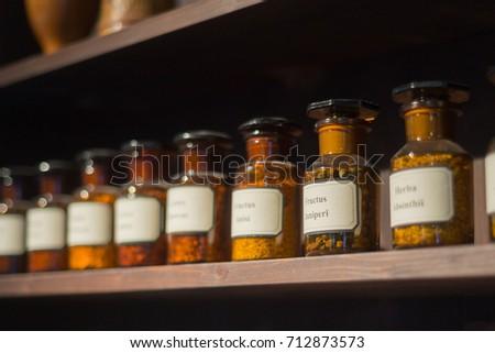 Vintage alchemy chemistry workshop rack shelf and glass vials ingredients #712873573