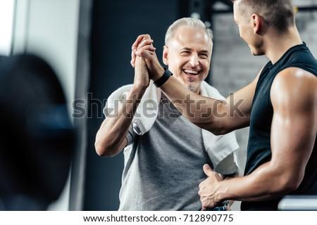 senior sportsman giving highfive to trainer in sport center #712890775