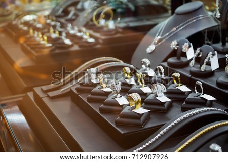 Gold jewelry diamond shop with rings and necklaces luxury retail store window display showcase  Royalty-Free Stock Photo #712907926