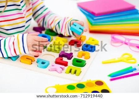 Child doing homework for school at white desk. Wooden educational abc toy puzzle for kids. Happy back to school student. Kid learning alphabet letters. Little girl with school supplies and books. #712919440