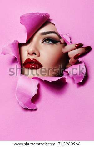 the face of a young beautiful girl with a bright make-up and with plump red lips peeks into a hole in pink paper.