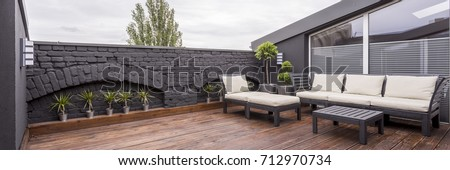 Panorama view of modern rooftop terrace with dark wood deck flooring, plants, brick fence and black garden furniture