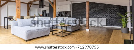 Modern loft open space apartment with wooden beams and floor, simple modern furniture, gray sofa, coffee table, brick wall, view from the living room Royalty-Free Stock Photo #712970755