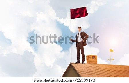 Businessman standing on house roof and holding red flag. Mixed media #712989178