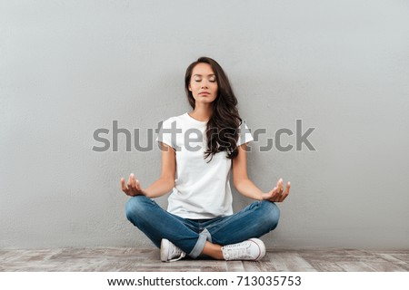 Beautiful young asian woman sitting in yoga position and meditating isolated over gray background #713035753