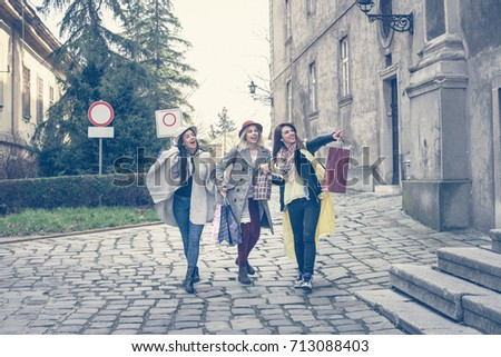 Young females best friends doing shopping on the streets. Women running trough street. #713088403