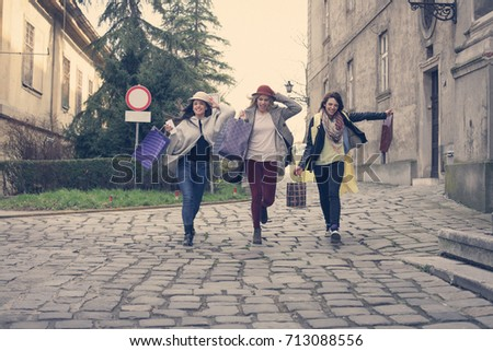 Young females best friends doing shopping on the streets. Women running trough street. #713088556