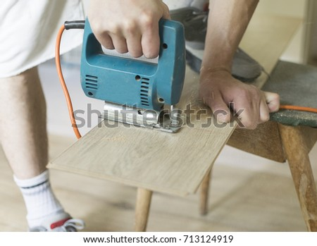 Man  using an electric saw to cut a plank. #713124919