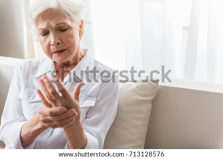 Elderly lady is enduring strong ache #713128576