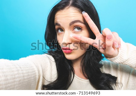 Young woman taking a selfie on a blue background #713149693