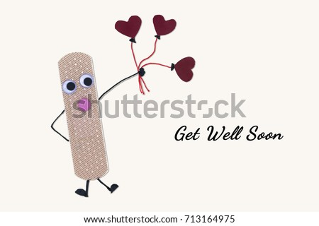 Send get well soon red heart balloons and wish fast healing. Handmade craft card design by cute bandage, red sticker paper.Top view and flat lay. Natural color and selective focus.Copy space for text. #713164975