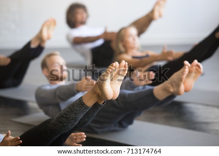 Group of young sporty people practicing yoga lesson with instructor, stretching in Paripurna Navasana exercise, balance pose, working out, indoor close up image, studio, focus on feet  #713174764