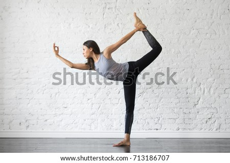 Young attractive woman practicing yoga, stretching in Natarajasana exercise, Lord of the Dance pose, working out, wearing sportswear, gray tank top, black pants, indoor full length, studio background  #713186707