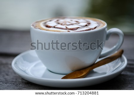 Latte coffee on white wooden table, latte art, in day light  #713204881