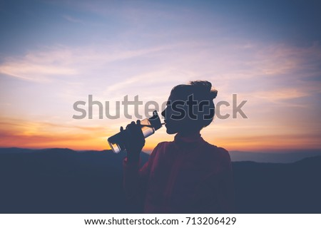 Silhouette of athletic woman drinks water while relaxing during training in the mountains at sunset. Sport tight clothes. #713206429