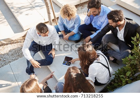 Coworkers sitting outside using tablet and discussing #713218255